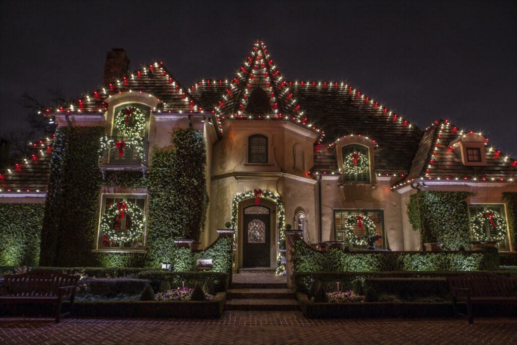 house outlined with red and white christmas lights with wreath and garland