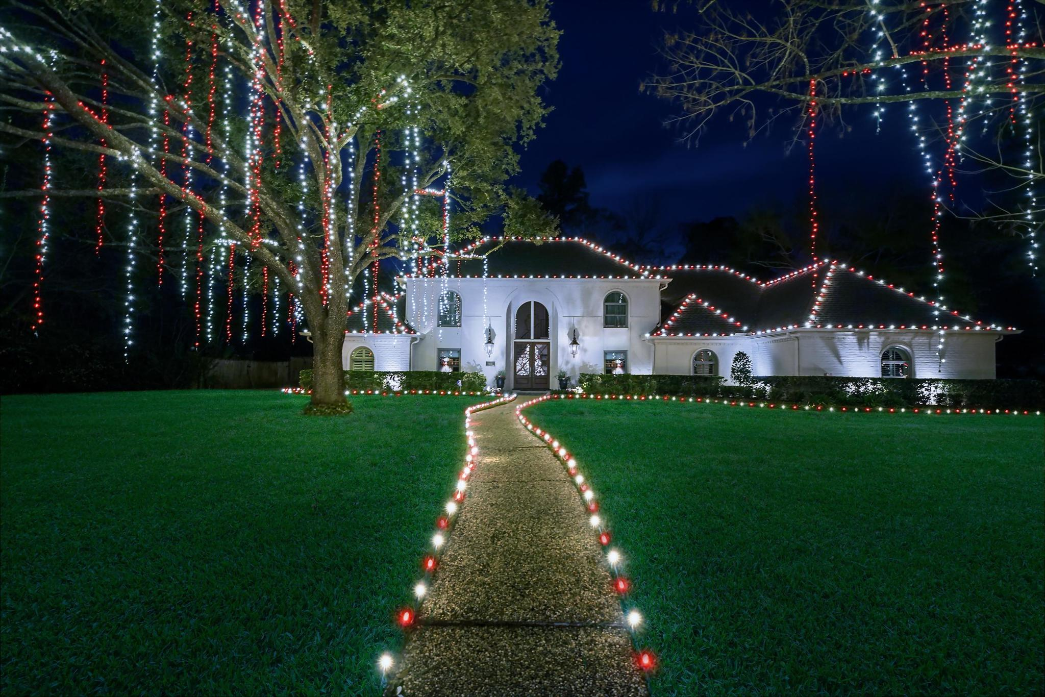 red and white christmas lights on home, walkway, and tree by The Perfect Light