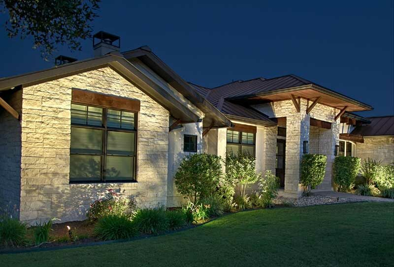 exterior lighting Tan and brown home with landscape lighting by The Perfect Light